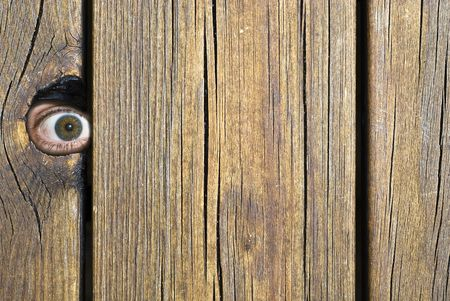 Eye peeking through hole in fence! Stock Photo - 3373802