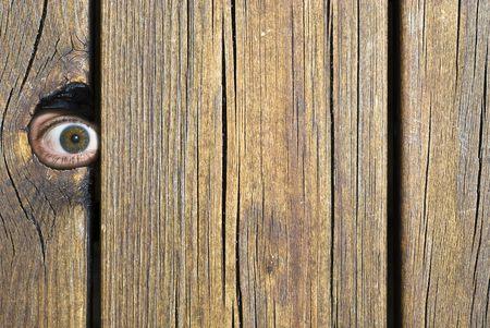 Eye peeking through hole in fence! Stock Photo - 3373802