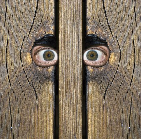 Eyes watching something through hole in a fence Standard-Bild