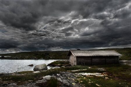A lightning strikes over an old shed by a lake in the norwegian mountains