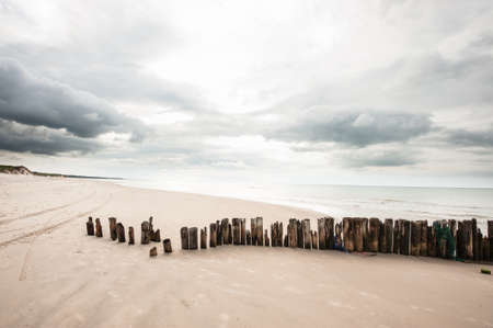 Poles in the sand at the beach in Tversted in Denmark Standard-Bild