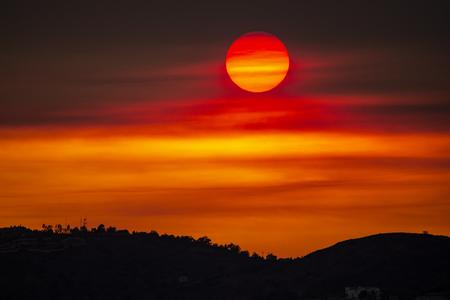 The sun sets through the smoke of a major wildfire