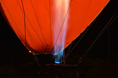 The flames caused by the gas spur up to blow the air into the balloon. The backdrop is black and orange.