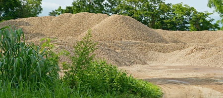 aggregates: The river gravel pile is sold for cement use in construction.
