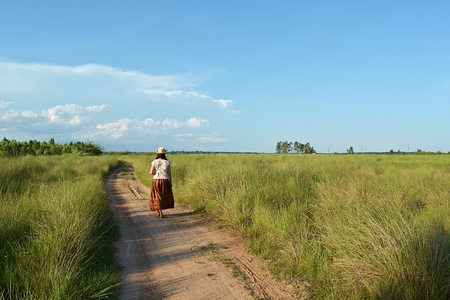 was: The girl in a brown skirt wearing a hat was walking on a dirt road. The blue sky is the backdrop