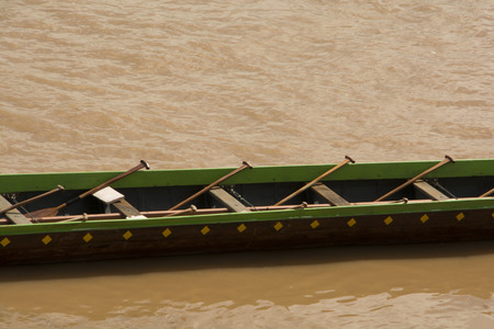 Long boat floated in the river. While the rowers on the rest. Waiting for the match Focus on the bilge and the paddle. The river background is turquoise.
