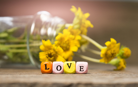 Love letter On the wooden floor there is a backdrop of flowers in a bottle. Add artificial light pink Focus on the word love