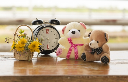 Teddy bear, alarm clock and flower basket on wooden floorBackground blurred Stock Photo