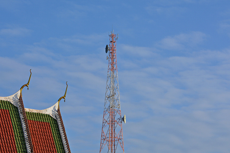 Phone Antenna And the church in Buddhism. Blue sky and fluffy white clouds are in the background. Stock Photo