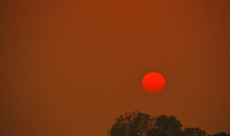 The red sun in the evening in a red-tone theme and the sky begins to darken. Banco de Imagens