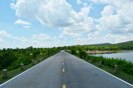 A road that is beautiful in the provinces of Thailand. Stretching straight ahead With blue sky and mountains as background
