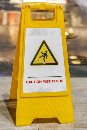 caution wet floor sign at a sidewalk photo