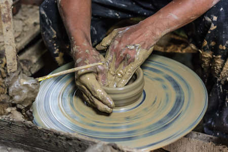 dirty hands: dirty hands making pottery in clay on wheel