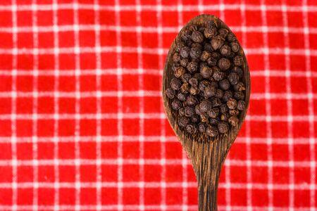 peppercorn: black pepper on wooden spoon