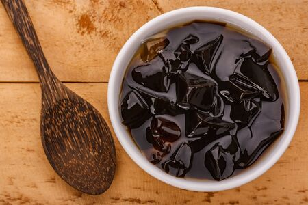 grass jelly or vegetable jelly on wood background Banco de Imagens