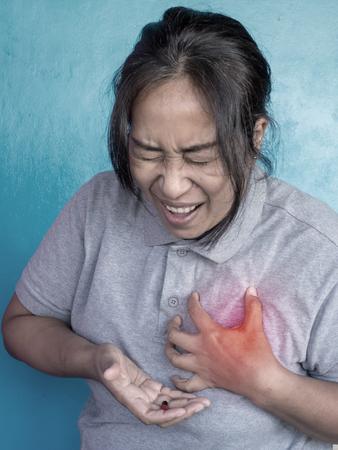 Asian female having chest pain, heart attack. Stock Photo