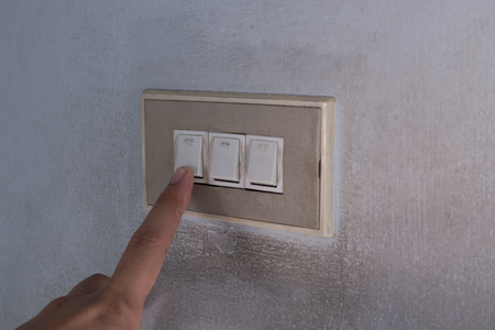 point finger touch the light switch to turn it off. Energy saving concept. Banco de Imagens