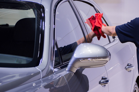woman cleaning car with microfiber cloth.
