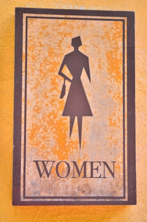women toilet sign on yellow wall photo