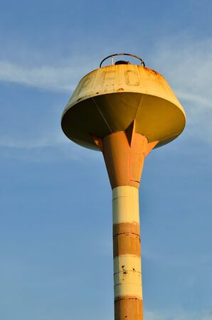rusty water tank tower and blue sky photo