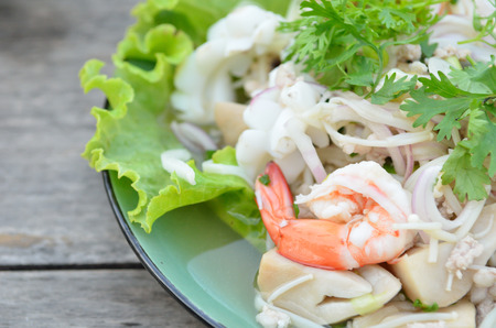 Thai spicy salad with seafood on the plate photo