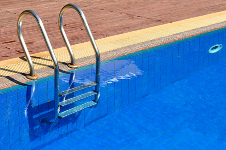 Blue swimming pool with metal ladder photo