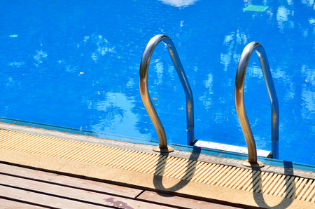Blue swimming pool with metal ladder Stock Photo