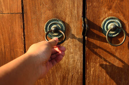 Hand on a handle wooden door to open or close it. Stock Photo