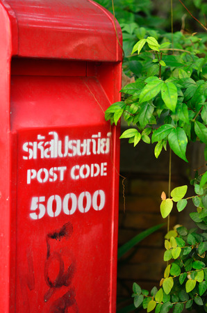 red post box set against nature background at Chiang mai Thailand