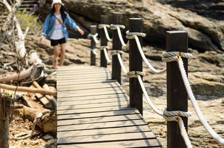 Women walk on brown wooden bridge at sea