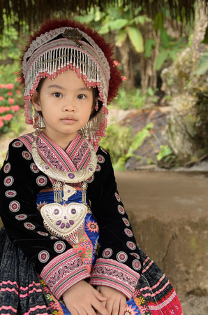 Thai girl wear costume traditional of ethnic hmong for take photo in garden at Doi Pui Tribal Village and National Park in Chiang Mai, Thailand.