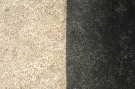 Sunlight and shadow on cement floor . Contast of color