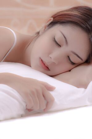 beautiful young woman sleeping on a bed in a bedroom at home photo