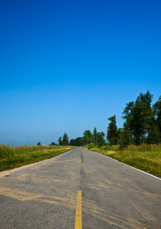 long road stretching out into the distance under a dramatic\ blue sky
