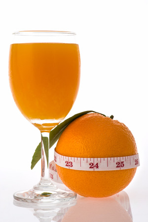 glass with fresh orange juice near the one orange  photo
