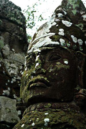 Aged Ancient Big Buddha Face on Ancient Cambodia Ruins photo