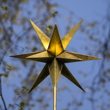 three dimensions: A golden glnzender star in three dimensions in the park against blue sky.