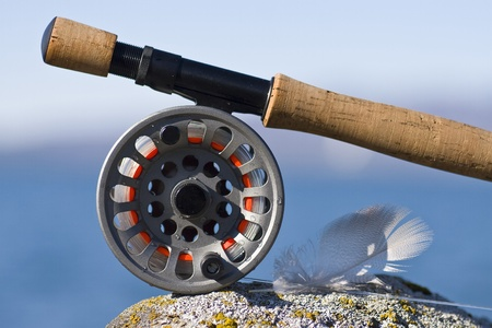 sport fishing: Fly rod, fly reel and a feather on a rock