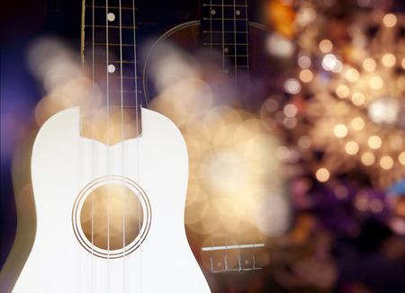 adentro y afuera: Guitarra ac�stica blanca delante de una guitarra ac�stica de color marr�n en fuera de foco y efecto de iluminaci�n con el anillo de donut.