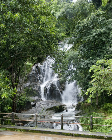 fountainhead: Stream of Waterfall lash down Torrential Water flow hit rock Around are wet leafage and wet tree Green forest in Rainy Season