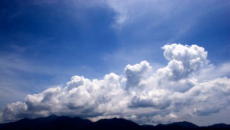 joyfully: White cloud on joyfully Blue Sky.Cloud full on sky look still and reticence.Below os frame is mountain range. Stock Photo