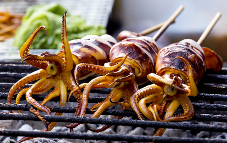 bar b que: Three Grilled squid on gridiron,Delicious bar b Que sea food. Stock Photo
