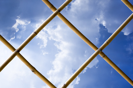 thru: Expand white cloud on blue sky see thru bamboo fence.Bright sunlight from left side.