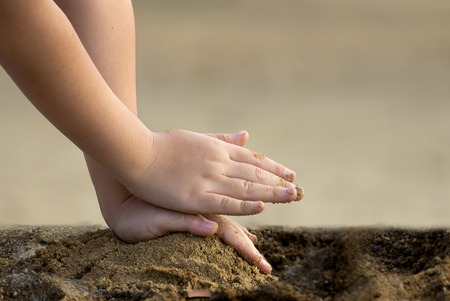 pat: Child piling up the sand, so pat and press sand with two hand.crop only hand. Stock Photo