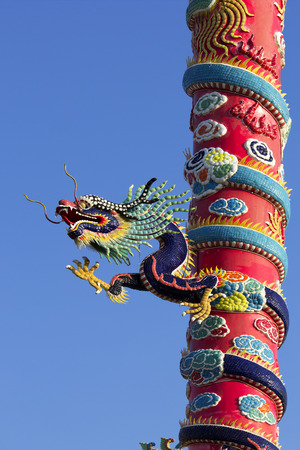 entwine: China Dragon Climb up and  entwine around pillar.Background is clear blue sky.