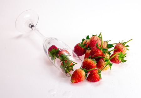tall glass: Fresh Strawberry and tall glass. A little shadow and water droplet on white ground. Stock Photo