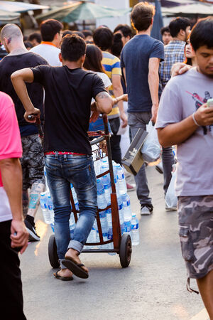 foodstuff: BANGKOK,THAILAND-FEBRUARY 9 2015:Labourer and wheelbarrow to send water at Jatujak Market or JJ Market that famous and celebrated tourist attraction with souvenir,appliance,art work,garment,foodstuff. Editorial