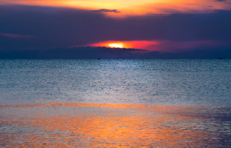 come up: Glittering sea and calmly wave at sunrise, a little tidal. Sun just come up. Dazzling reflection from sunlight on sea surface.