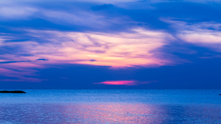 come up: Blue sea and calmly wave at sunrise, a little tidal. Sun just come up. Glittering reflection from sunlight on sea surface.