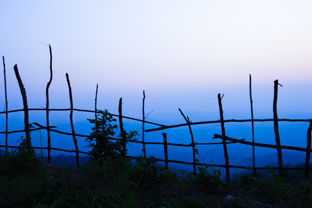widely: Dark tree and fence stick in shadow at foreground.Mountain at background.Sun nearly go down. Stock Photo